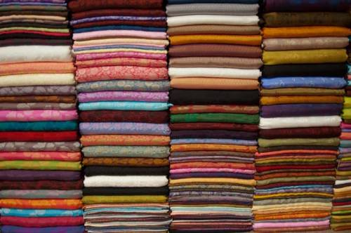 Pile of brightly colored fabrics in Dong Xuan Market.