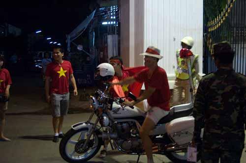 Vietnam football fans climb on Vientiane police motorbike