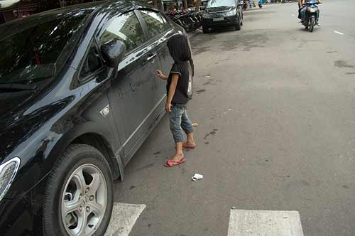girl writing on car, Ho Chi Minh City, Vietnam