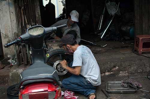 working on motorcycle, Saigon, Vietnam