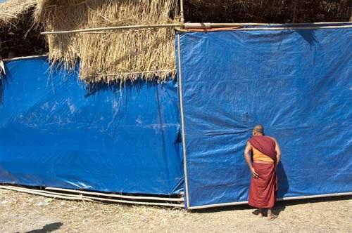 monk peering in kickboxing tent