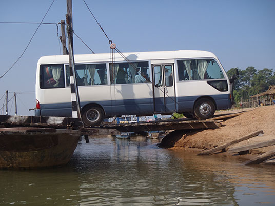 mini bus being unloaded at Ban Muang, Champasak, Laos