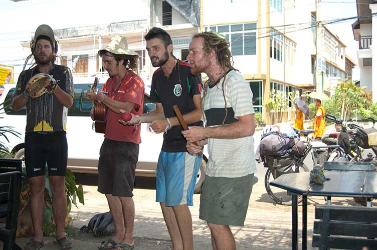 French cyclists serenading customers at Delta Coffee, Pakse, Laos