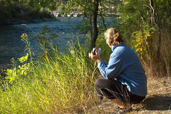 Sue Kronen having morning coffee while watching the river flow