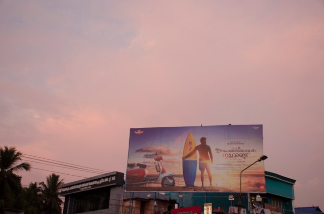 sunset and a billboard near Trivandrum, India
