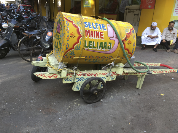 brightly coloured portable water tank in Mumbai, India